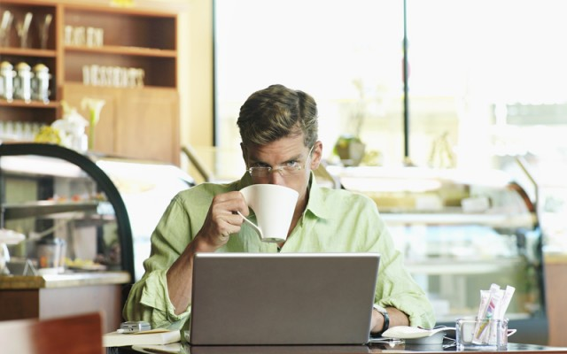 Man sitting at cafe table, using laptop, drinking mug of coffee, front view, portrait